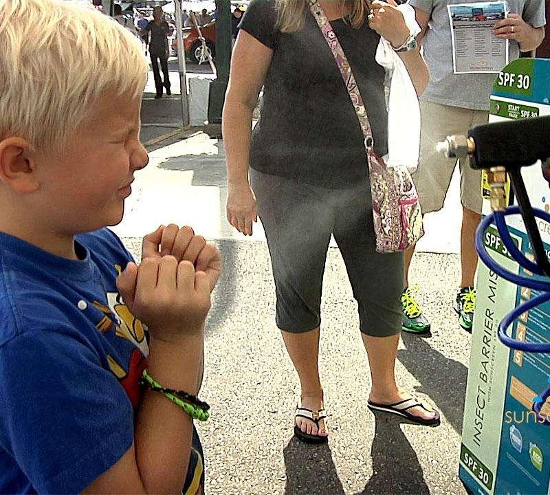 Boy Getting Sunscreen Mist Applied